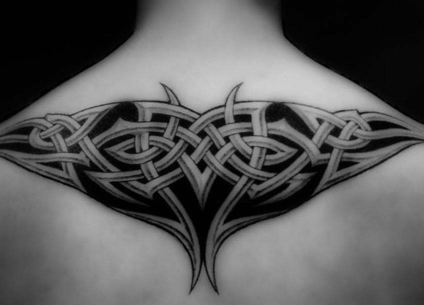 Black tattoo braided pattern  on upper back