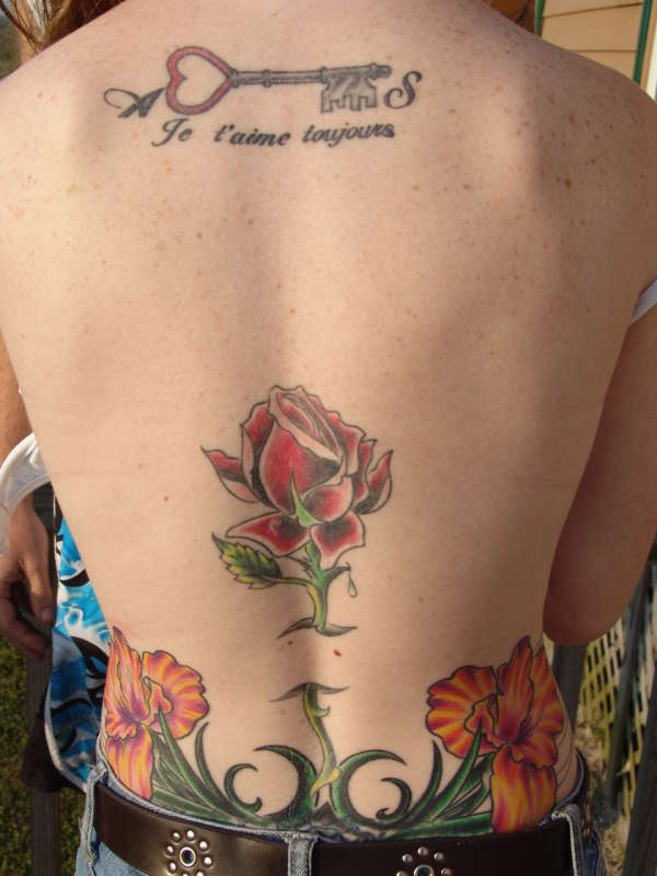 Love key tattoo above the  flowers on upper back