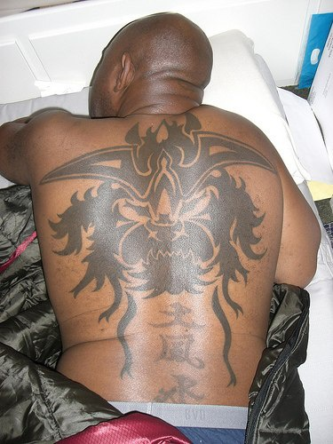 Horned devil   on upper back black and  morose  tattoo