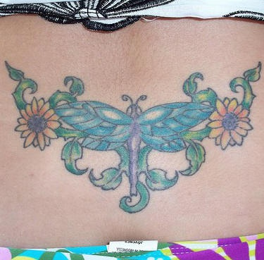 Beautiful tattoo on upper back dragonfly in flowers