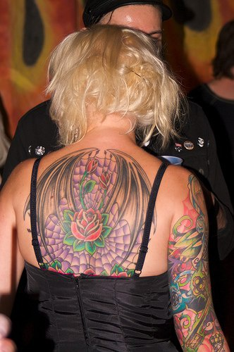 Beautiful roses on upper back in winged web tattoo