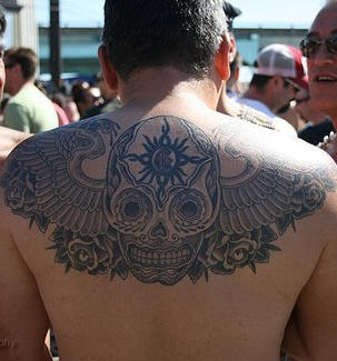 Skull on upper back decorated tattoo with wings