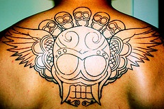On upper back winged skull with  little skulls  tattoo