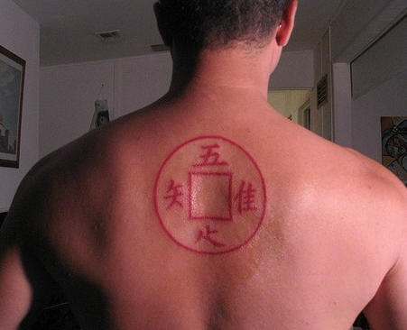 Square and  hieroglyphs on upper back red tattoo
