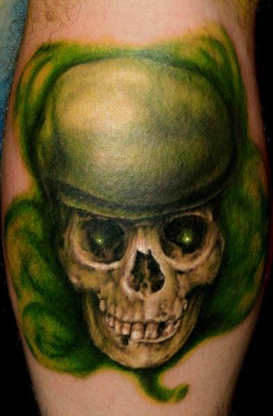 Leg tattoo, green styled, awful skull, teethy