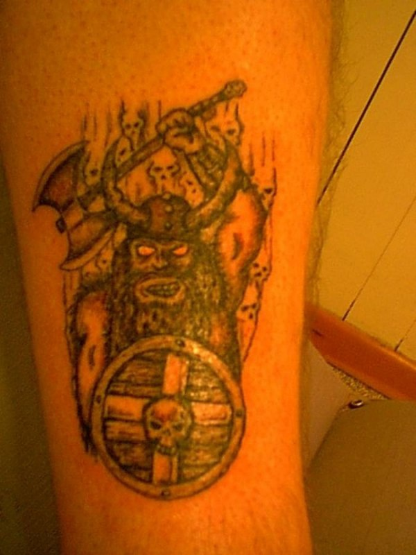 Angry viking with axe and circle shield tattoo