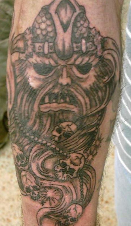 Tattoo of viking head with dark eyes and skulls