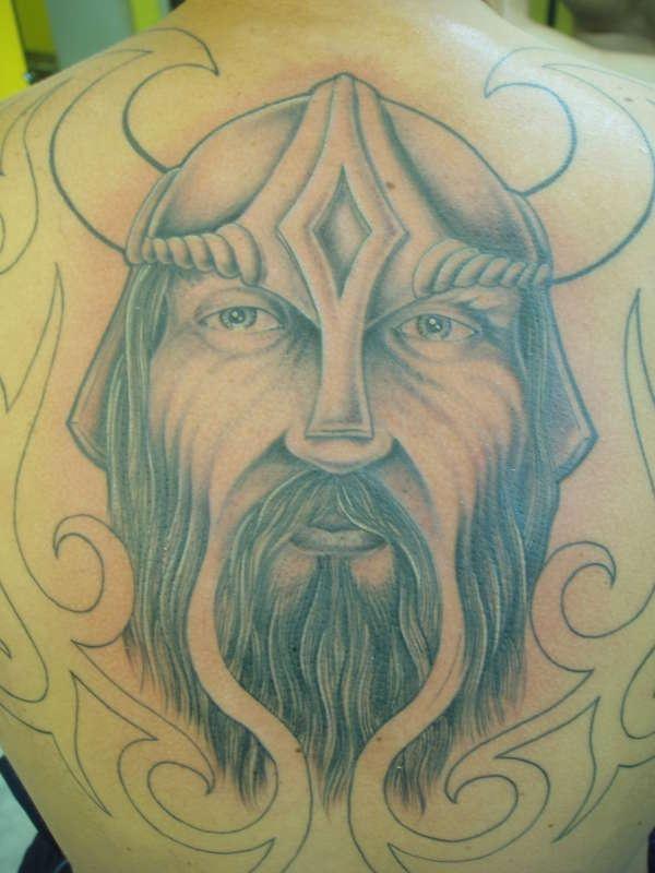 Viking warrior head in horned helmet big tattoo on back