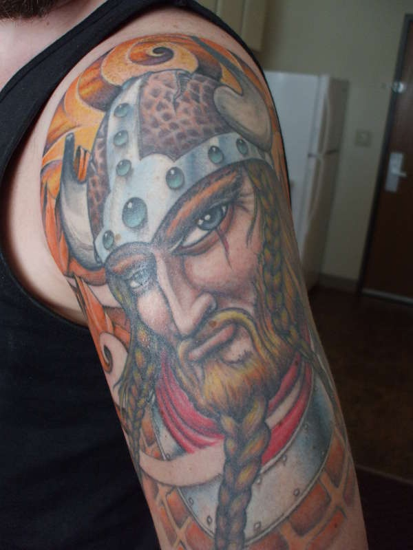 Colorful tattoo of viking with beard braid in a braid