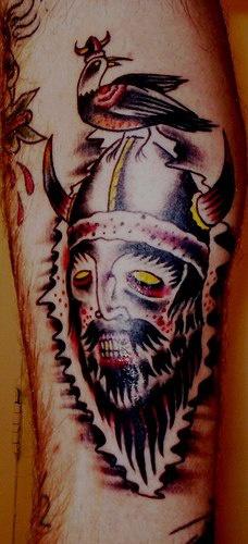 Viking warrior in helmet tattoo with bird on his head
