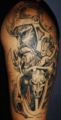 Big shoulder tattoo of viking and animal skull