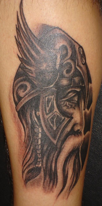 Sad warrior with long beard in helmet with wings tattoo