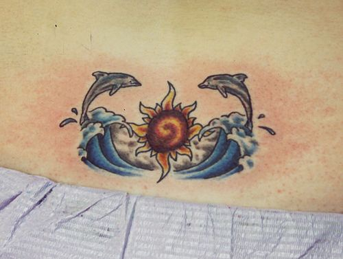 Two dolphins in the waves on sunset  tattoo