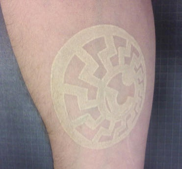 White ink tattoo with circle sign