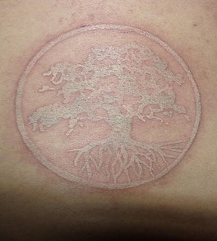 White ink tattoo with tree on circle