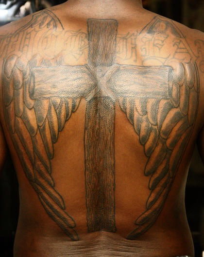 Winged cross tattoo on back