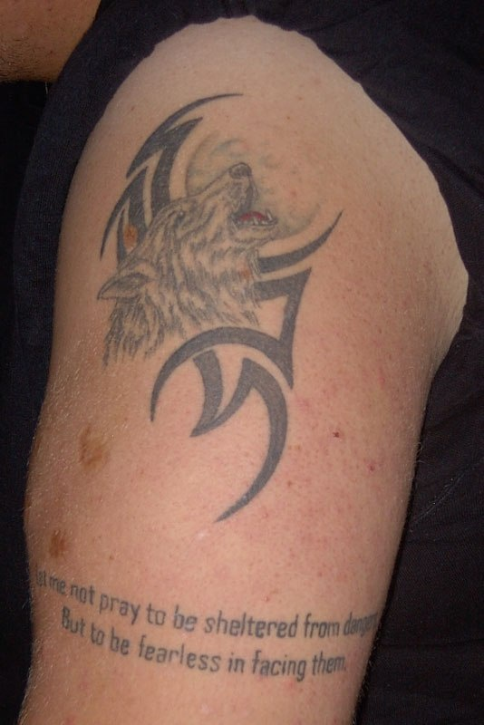 Tattoo with wolf howling on the moon and tribal sign