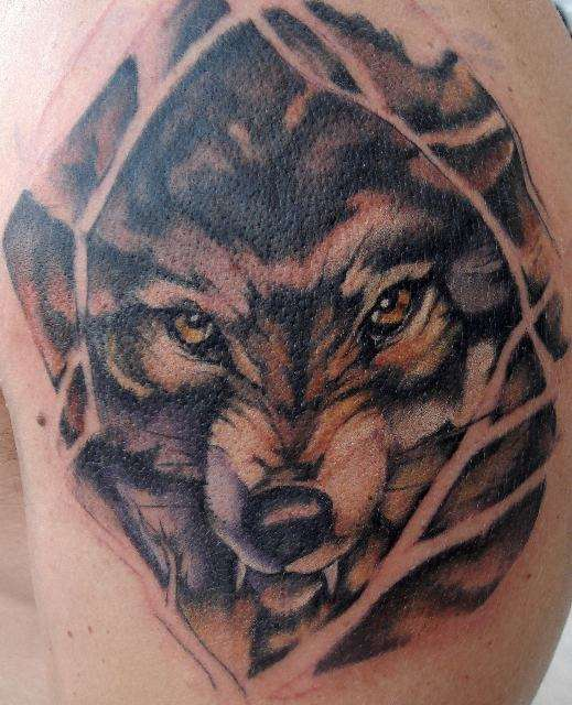 Angry wolf with yellow eyes tattoo