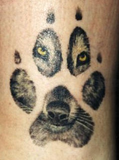 Wolf paw tattoo with yellow eyes