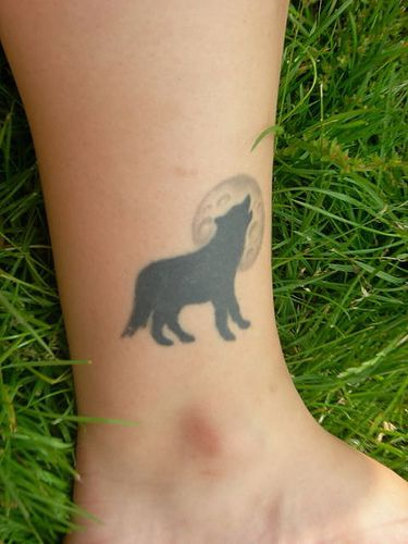 Tatuaggio piccolo sulla caviglia il lupo nero che ulula alla luna