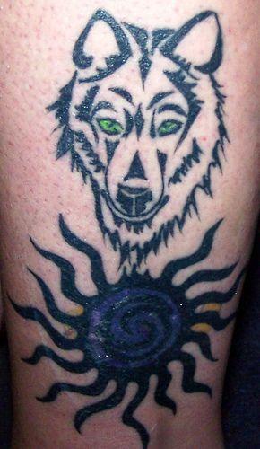 Green eyed wolf tattoo with dark blue sun