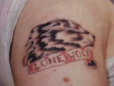 Small wolves tattoo with inscription lone wolf