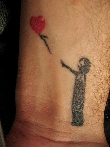 Tatuaggio sul polso il bimbo piccolo con pallone in stile Banksy art