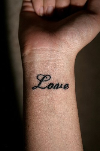 Love calligraphic tattoo on wrist