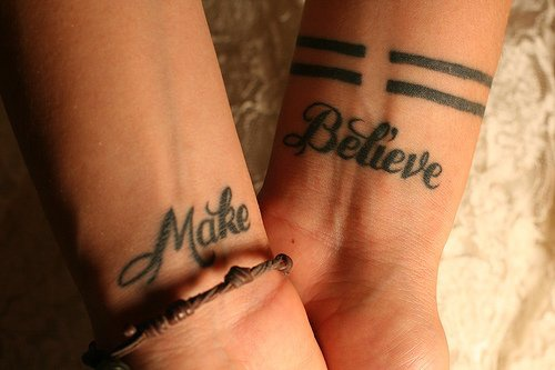 Calligraphic tattoo with words Make Believe on both wrists