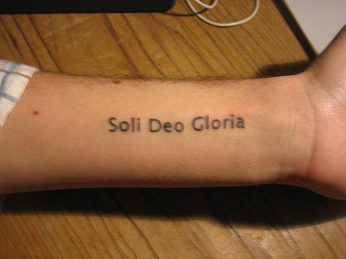 """Tatuaggio lungo sil braccio la scritta &quotSoli deo gloria"""""""
