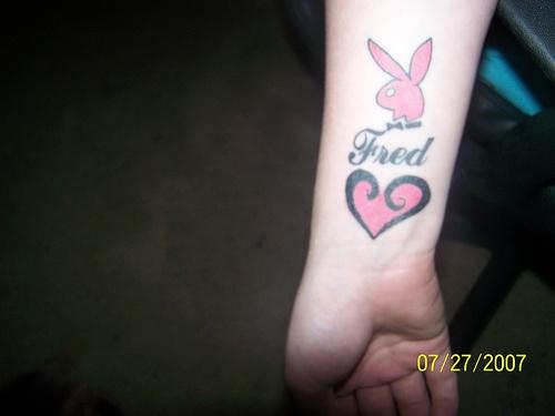 Tatuaggio sul polso il segno rosa di Playboy & il cuore rosa