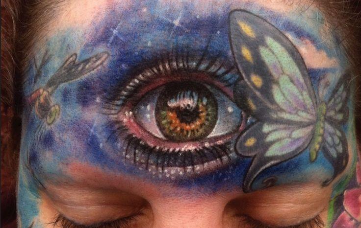 Tatuaggio colorato sul fronte l&quotocchio e la farfalla