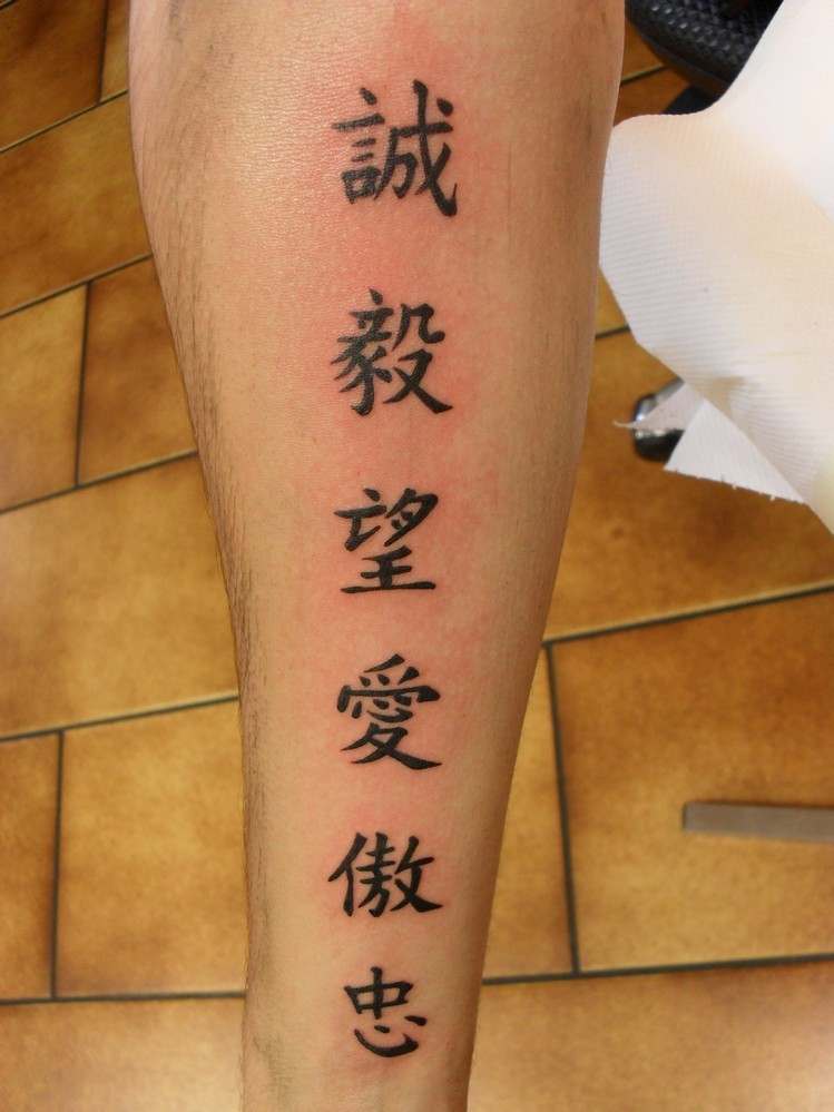 Tattoo of six chinese symbols on leg
