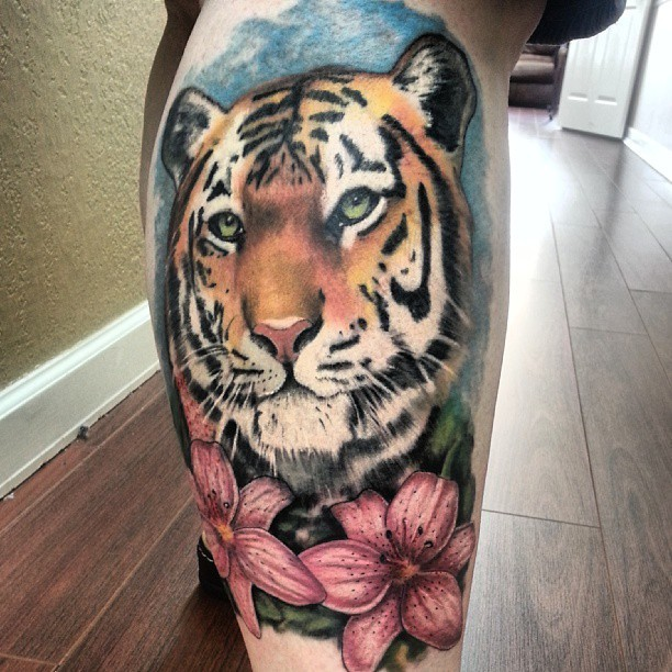 Coloured tattoo of tiger on the calf muscle