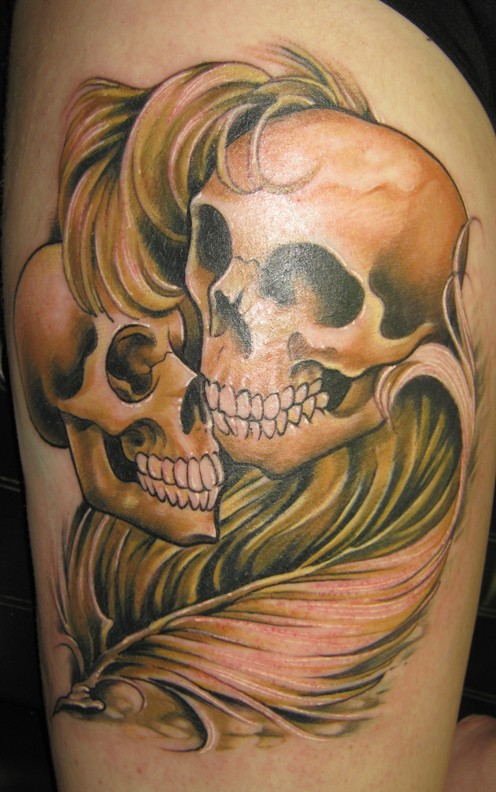 Two skulls with feather tattoo