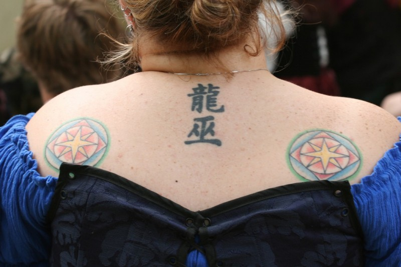 Tattoo with stars and chinese symbols on back