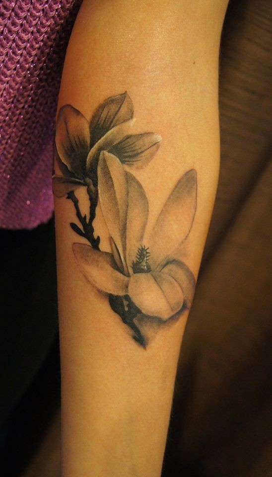 Tender black-and-white magnolia flower tattoo on arm