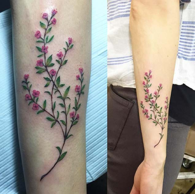Tender blossoming branch with tiny pale pink flowers tattoo on arm