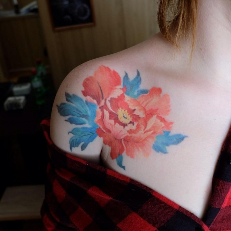 Tender pale red peony flower tattoo on shoulder of young lady