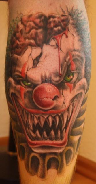 Terrible clown with a broken skull tattoo
