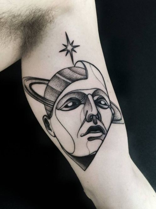 Terrifying blackwork style biceps tattoo of mystical head with planet and star by Michele Zingales