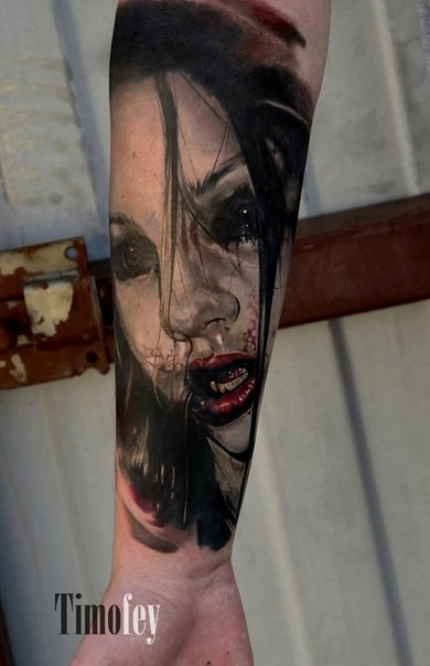 Terrifying looking colored arm tattoo of bloody vampire woman