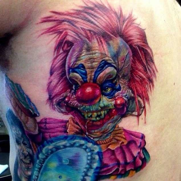 Terrifying looking colored clown tattoo on back