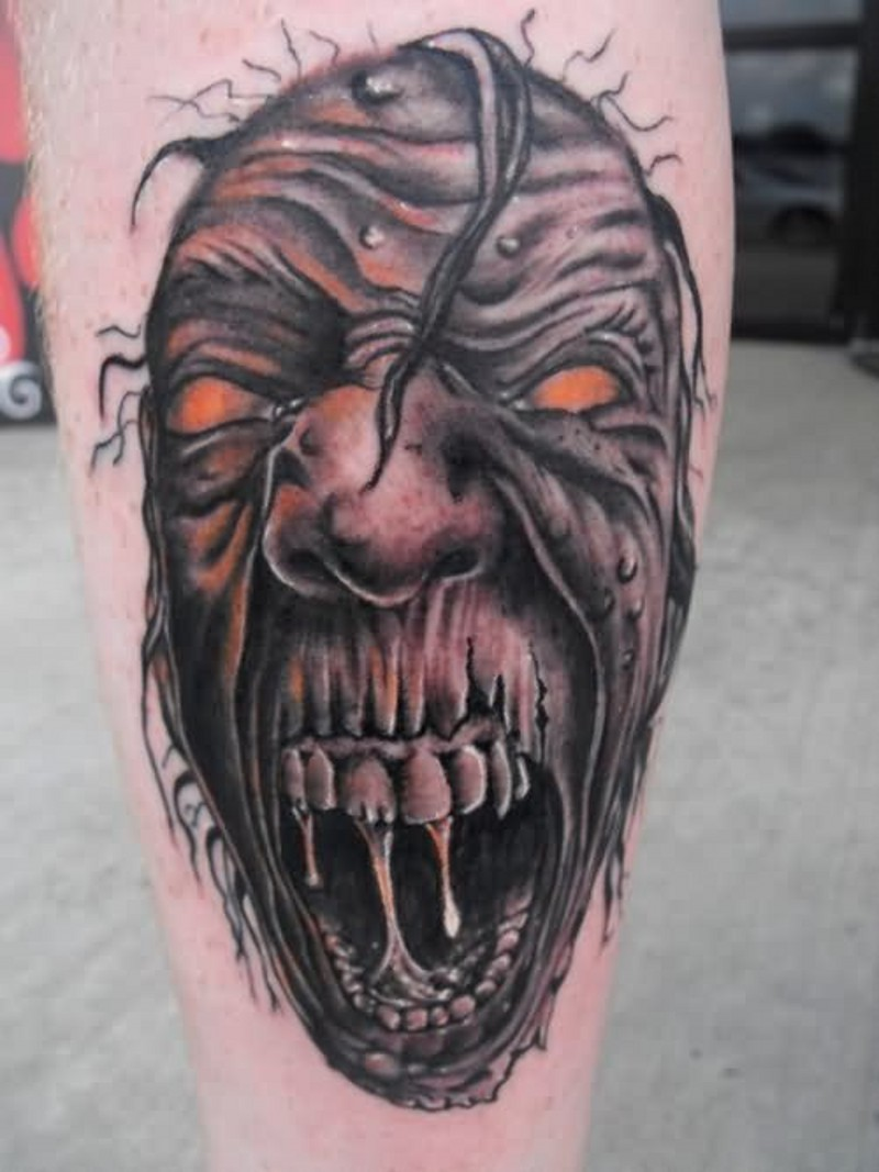 Terrifying looking colored leg tattoo of stunning monster face
