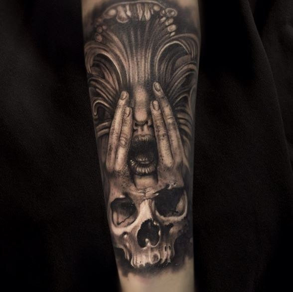 Terrifying looking detailed arm tattoo of interesting face with human skull