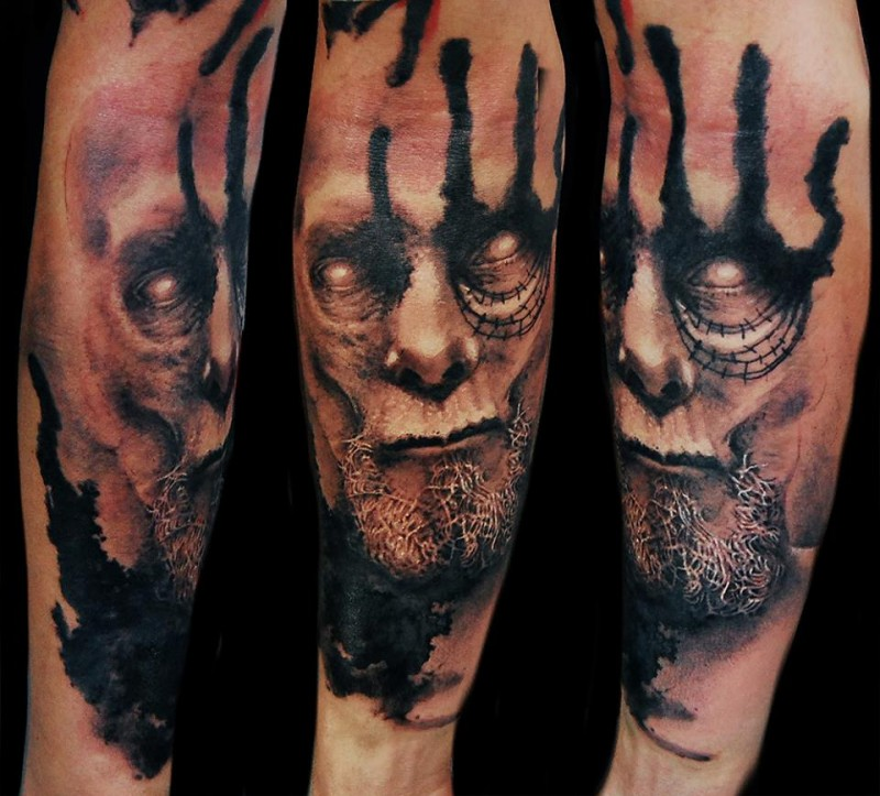 Terrifying looking forearm tattoo of demonic face with beard