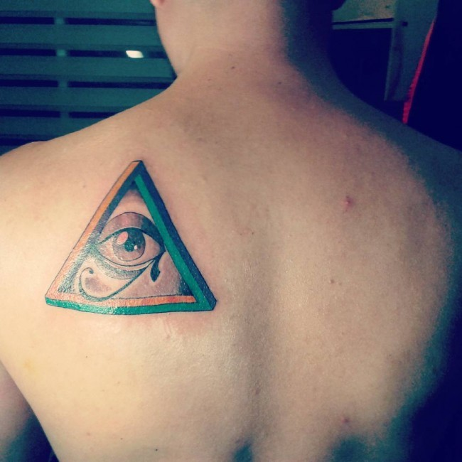 The Eye of Horus Egyptian ancient symbol in pyramid colored tattoo on shoulder blade