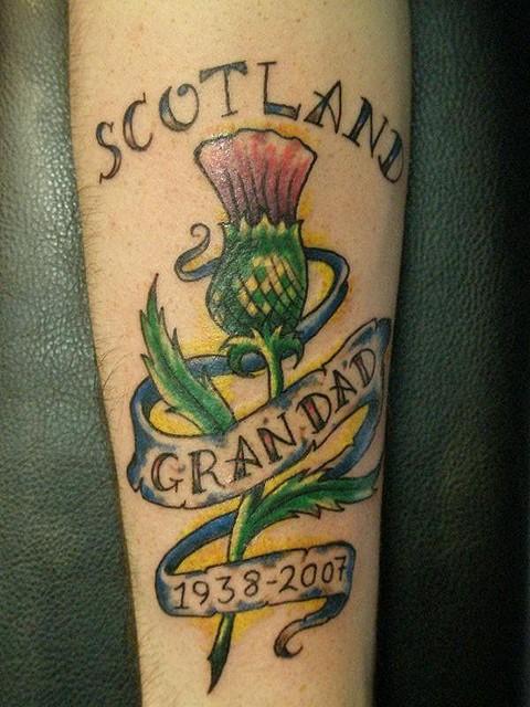 fiore cardi scozzese con lettere tatuaggio su braccio