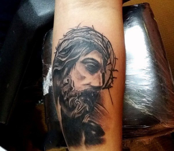 Thoughtful Jesus Christ in crown of thorns religious forearm tattoo
