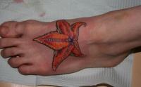 Beautiful orange leave-shaped starfish tattoo on foot